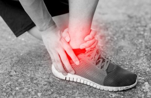 Runner touching painful twisted or broken ankle. Athlete runner training accident. Sport running ankle sprain.